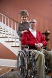 Couples aînés à la maison, homme dans le fauteuil roulant Images libres de droits