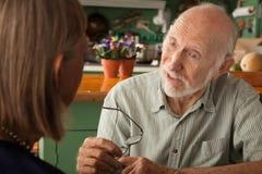 Couples aînés à la maison se concentrant sur l'homme Image libre de droits