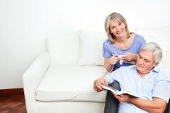 Couples aînés à la maison sur le divan Photo libre de droits