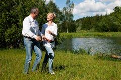 Couples aînés à un lac en été images stock