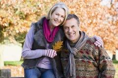 Couples aînés affectueux sur la promenade d'automne Image stock