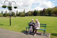 Couples aînés affichant un journal sur un banc de stationnement Image libre de droits