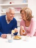 Couples aînés appréciant la boisson chaude dans la cuisine Photos stock