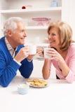 Couples aînés appréciant la boisson chaude dans la cuisine Photographie stock