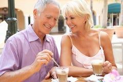 Couples aînés appréciant le café et le gâteau Photo stock