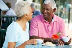 Couples aînés appréciant le casse-croûte au café extérieur Images libres de droits