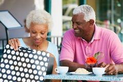 Couples aînés appréciant le casse-croûte au café extérieur Photo stock