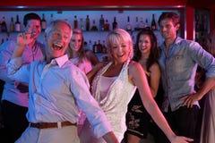 Couples aînés ayant l'amusement dans le bar occupé Photos libres de droits