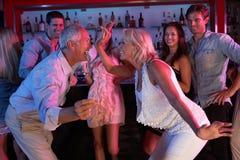 Couples aînés ayant l'amusement dans le bar occupé Photo stock
