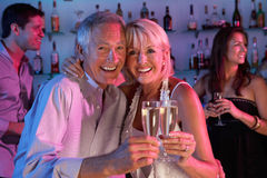 Couples aînés ayant l'amusement dans le bar occupé Photographie stock