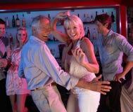 Couples aînés ayant l'amusement dans le bar occupé Image stock