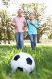 Couples aînés ayant l'amusement jouer au football Image stock