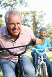 Couples aînés ayant l'amusement sur le vélo des enfants Image libre de droits