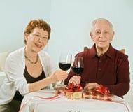 Couples aînés ayant une glace de vin Photos libres de droits