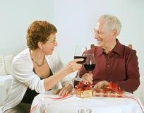 Couples aînés ayant une glace de vin Image stock