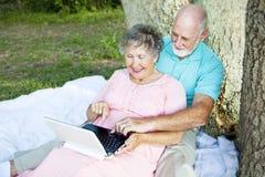 Couples aînés calculant à l'extérieur Photos stock