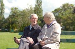 Couples aînés causant sur le banc de stationnement Photo libre de droits