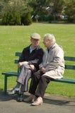 Couples aînés causant sur le banc de stationnement Image libre de droits