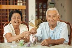 Couples aînés comptant l'argent Image stock