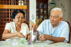 Couples aînés comptant l'argent Images stock