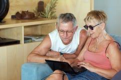 Couples aînés contrôlant l'ordinateur portatif Photos stock