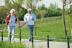 Couples aînés courant en stationnement image libre de droits