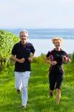 Couples aînés courant pour le sport Image stock