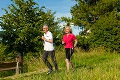 Couples aînés courant pour le sport Images stock