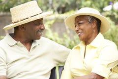 Couples aînés détendant dans le jardin ensemble Photos stock