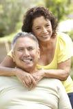 Couples aînés détendant dans le jardin ensemble Photo stock