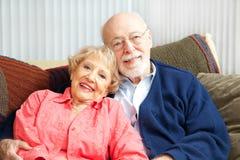 Couples aînés détendant sur le divan Photo stock