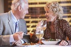 Couples aînés dînant à un restaurant images stock
