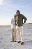 Couples aînés dans des chandails ensemble sur la plage Images libres de droits