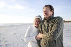 Couples aînés dans des chandails ensemble sur la plage Image stock