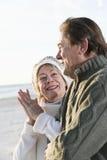 Couples aînés dans des chandails ensemble sur la plage Photos libres de droits