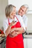 Couples aînés dans la cuisine avec du vin Photographie stock