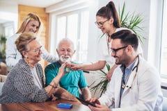 Couples aînés dans la discussion avec le visiteur de santé à Image libre de droits