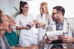 Couples aînés dans la discussion avec le visiteur de santé à Photos stock