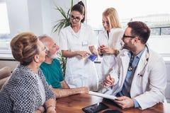 Couples aînés dans la discussion avec le visiteur de santé à Photographie stock libre de droits