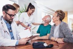 Couples aînés dans la discussion avec le visiteur de santé à Photo stock