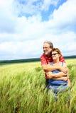 Couples aînés dans le domaine de blé Photographie stock