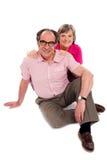 Couples aînés de sourire posés sur l'étage. Pose Photos libres de droits