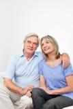 Couples aînés de sourire sur le divan Photographie stock libre de droits