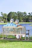 Couples aînés de vue arrière se reposant sur le banc de stationnement Photo stock