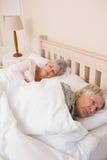 Couples aînés dormant dans le bâti Photos stock
