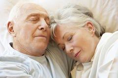 Couples aînés dormant dans le bâti Image stock