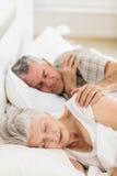 Couples aînés dormant dans le bâti Images stock
