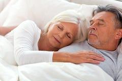 Couples aînés dormant dans le bâti Image libre de droits