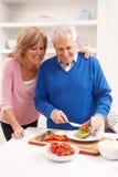 Couples aînés effectuant le sandwich dans la cuisine Photographie stock