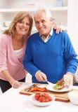 Couples aînés effectuant le sandwich dans la cuisine Image libre de droits